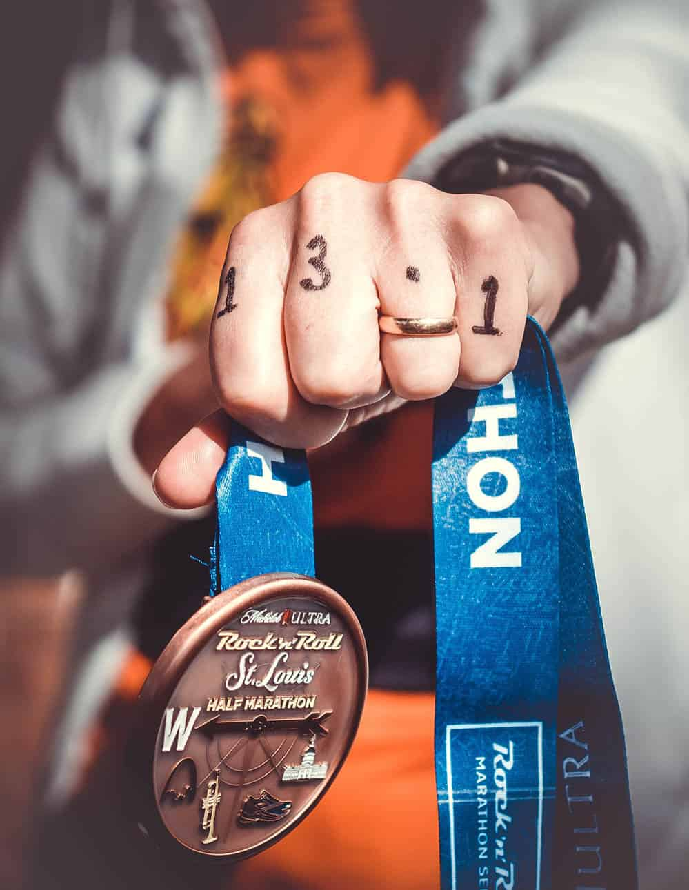 runner displaying his bling trophy medal after winning half marathon
